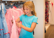 Little girl shopping in clothes store. Child chooses dress at clothes shop. Stock Photos