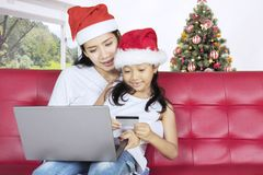 Little girl shopping online with her mother. Christmas holiday concept. Little girl shopping online with her mother while sitting on the couch Stock Image