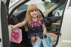 Little girl with shopping out of the car Stock Photography