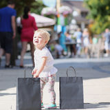 Little girl in shopping outlet village Stock Photos