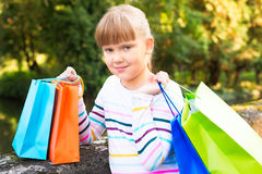 Little  girl  after shopping in the park Stock Photo