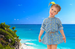 Little girl in a short blue dress on a sea background. Stock Photos