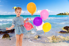 Little girl in a short blue dress on a sea background. Royalty Free Stock Image