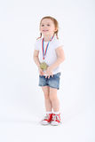 Little girl in shorts with medal on her chest stands and smiles Royalty Free Stock Photos