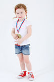 Little girl in shorts with medal on her chest stands Stock Image