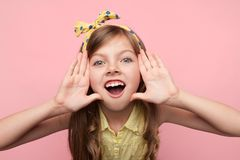 Little girl shouting at camera on pink Stock Photo