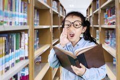 Little girl shouting in the library. Picture of little girl wearing glasses and holding a textbook while shouting in the library Royalty Free Stock Images