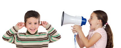 Little girl shouting through megaphone at a boy. Isolated over white Royalty Free Stock Photography