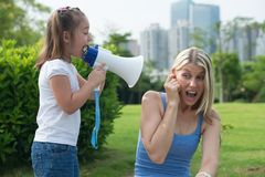 Little girl shouting into a megaphone. Girl screams into a megaphone for mom Stock Image