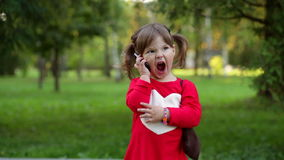 Little girl shouting into the phone in a park.  stock footage