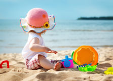 Little girl shouting at the sea with bucket. One year old girl shouting at the sea with bucket Royalty Free Stock Images