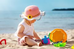 Little girl shouting at the sea with bucket. One year old girl sitting at the sea with bucket. Child outdoors at the beach in summer Stock Photography