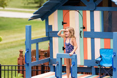 Little girl shouting to someone from playhouse Stock Images