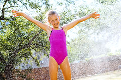 Little girl shouting under water sprayer. Royalty Free Stock Photos