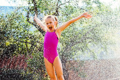 Little girl shouting under water sprayer. Royalty Free Stock Photography