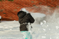 Little girl shoveling snow on home drive way. Beautiful snowy garden or front yard. Child with shovel playing outdoors in winter season. Family removing snow Royalty Free Stock Photo