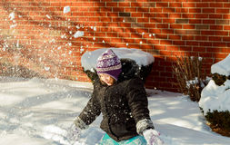 Little girl shoveling snow on home drive way. Beautiful snowy garden or front yard. Child with shovel playing outdoors in winter season. Family removing snow Royalty Free Stock Images