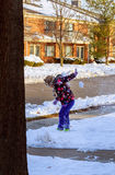Little girl shoveling snow on home drive way. Beautiful snowy garden or front yard. Little girl shoveling snow on home drive way. Child with shovel playing Stock Image