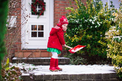 Little girl shoveling snow in winter Stock Photos