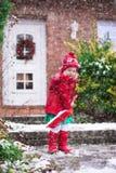 Little girl shoveling snow in winter Stock Image