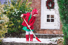 Little girl shoveling snow in winter Stock Photography