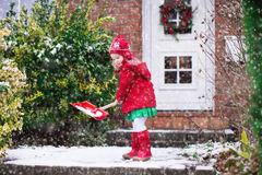 Little girl shoveling snow in winter Royalty Free Stock Image