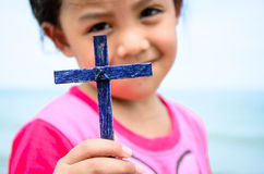 Little girl show the cross. The blue cross show on right hand of girl Stock Photos