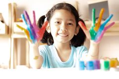 The little girl is showing color painted on hands. With smile and happiness. Select focus shallow depth of field and blurred background royalty free stock photos