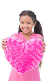 Little girl showing cushion in the shape of a heart Royalty Free Stock Photos