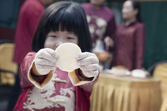Little girl showing dumpling wrapper in traditional clothing Royalty Free Stock Image