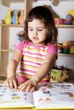 Little Girl Showing Figures in Book Stock Photography