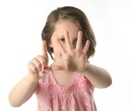 Little girl showing her age with fingers. Portrait of a little girl holding up six fingers in front of her face to show hold old she is, isolated on white Stock Photography