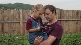 Little girl showing her dad a strange toy. Both are happy. They are staying outdoors on a summer cloudy day againts a wooden fence background stock video