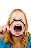 Little girl is showing her mouth. Through a magnifying-glass over white royalty free stock images