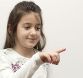 Little girl showing with the index finger Stock Images