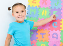 Little girl is showing letter E on the alphabet Stock Photos
