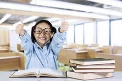 Little girl showing ok gesture in classroom Stock Photos