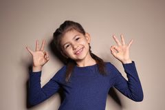 Little girl showing OK gesture in sign language on background. Little girl showing OK gesture in sign language on color background royalty free stock images