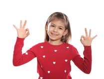 Little girl showing OK gesture in sign language on white. Background royalty free stock image