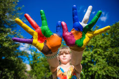 Little girl showing painted hands, focus on hands. Hand prints. Art and painitng concept royalty free stock image