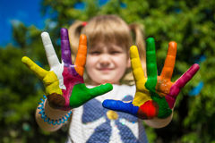 Little girl showing painted hands, focus on hands. Hand prints. Art and painitng concept stock image