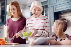 Little girl showing salad recipe to her mother and grandmother. Little assistant. Lovely little girl sitting at the kitchen counter and showing a tablet with a Stock Images