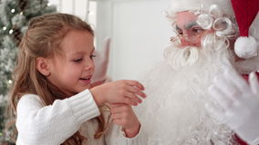 Little girl showing Santa Claus a magic trick with a disappearing finger stock video footage