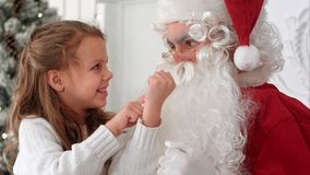 Little girl showing Santa Claus a magic trick with a disappearing finger. Closeup shot. Professional shot on BMCC RAW with high dynamic range. You can use it e Royalty Free Stock Images