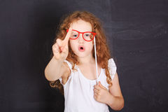 Little girl showing shaking finger saying no. School girl showing shaking finger saying no, near blackboard Stock Images