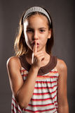 Little girl showing silence gesture Stock Image