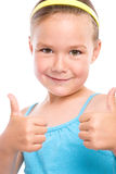 Little girl is showing thumb up gesture. Little girl dressed in blue is showing thumb up gesture using both hands, isolated over white Stock Images