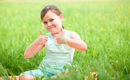 Little girl is showing thumb up gesture Royalty Free Stock Photos