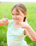 Little girl is showing thumb up gesture. While sitting on green grass Stock Photography