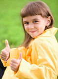 Little girl is showing thumb up gesture. Using both hands Royalty Free Stock Image